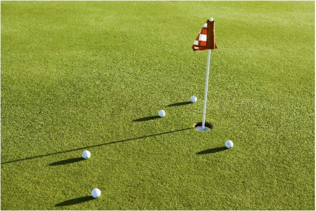 Golf balls on a putting green near the cup.